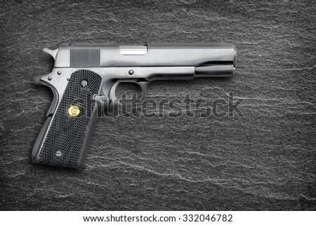 Semi-automatic gun isolated on black slate background  - stock photo
