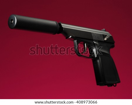 semi-automatic hand gun on red background, with silencer/suppressor - stock photo