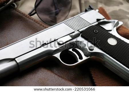 Semi-automatic handgun lying over a Leather handbag - stock photo