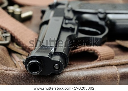 Semi-automatic handgun lying over a Leather handbag, 9mm pistol, Close-up Barrel. - stock photo