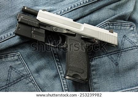 Semi-automatic handgun on blue jeans background, 9mm pistol. - stock photo