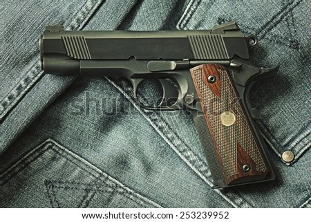Semi-automatic handgun on blue jeans background, .45 pistol. Process HDR detail. - stock photo