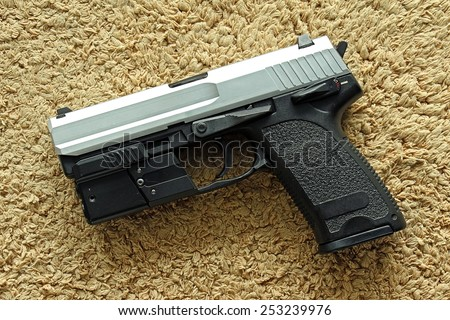 Semi-automatic handgun on carpet background, 9mm pistol. - stock photo