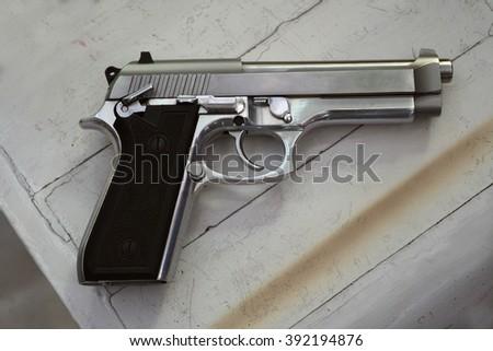 Semi-automatic handgun on grey wooden background - stock photo