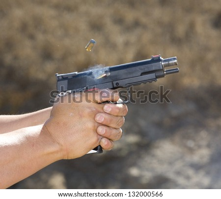 Semi automatic handgun that has ejected a case and is feeding another - stock photo