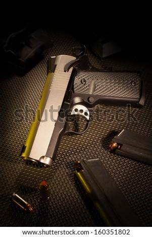 Semi automatic handgun with ammunition and magazines - stock photo