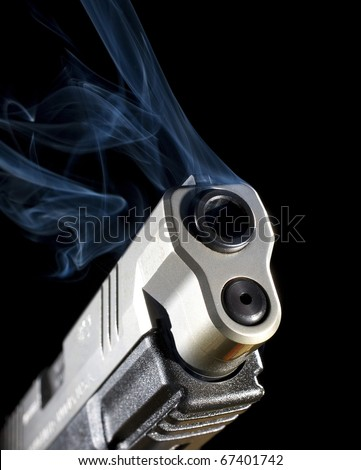 Semi-automatic pistol releasing smoke after a shot has been taken - stock photo
