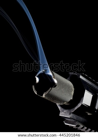 Semi automatic rifle on black with smoke coming from the barrel - stock photo
