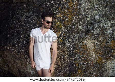 Semi dressed man in sunglasses against rock - stock photo