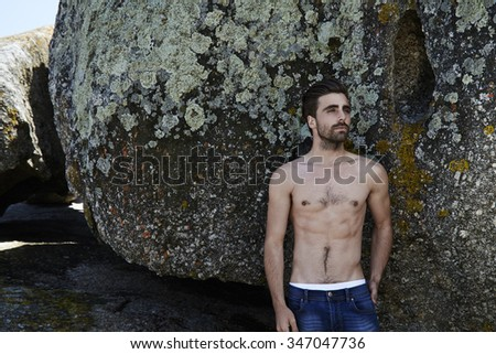 Semi dressed young man in front of rocks, looking up - stock photo