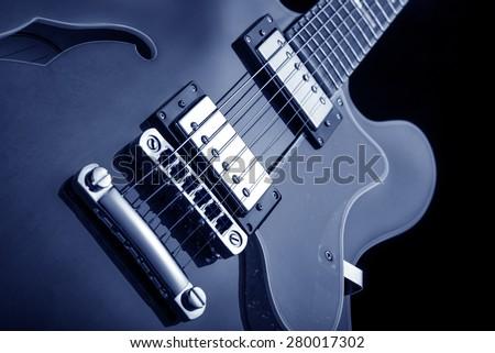 semi-hollow body electric guitar close up, blue image - stock photo