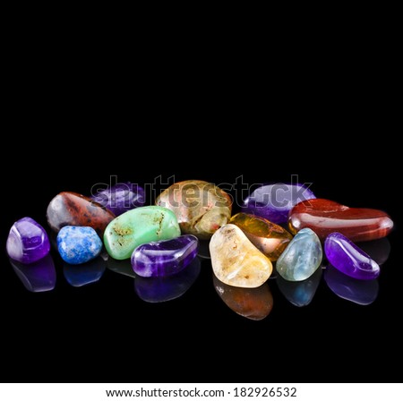 Semi-precious stones against black background with copy space for text  - stock photo