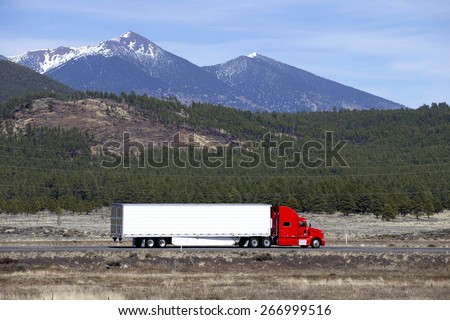 Semi truck going fast on mountain highway - stock photo