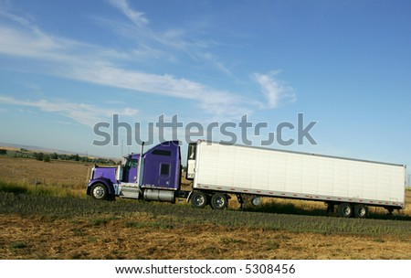 Semi truck going up hill on interstate highway - stock photo