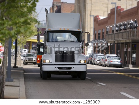 Semi Truck passing through Town - stock photo