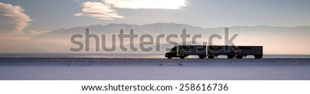 Semi Truck Travels Highway Over Salt Flats Freight Transport - stock photo