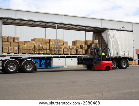 Semi truck with forklift driver - stock photo