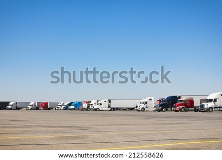 Semi-trucks sit at a rest stop parking lot.