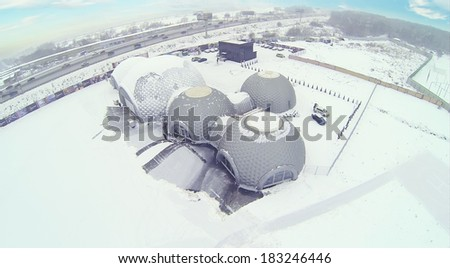 Semicircular hangar for helicopters on cloudy winter day. Aerial view - stock photo