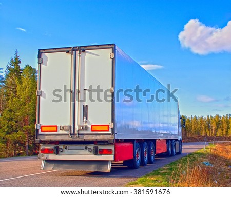 Semitrailer on the wood road in sunny day - stock photo