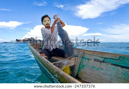 SEMPORNA, MALAYSIA - JULY 3 : Unidentified Sea Bajau's girl rowing a boat July 3, 2009 in Sabah, Malaysia. Children here do not attend school for lack of means and resources. - stock photo