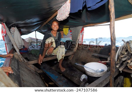 SEMPORNA, MALAYSIA - JULY 3 : Unidentified Sea Bajau's woman sit on a boat house on July 3, 2009 in Sabah, Malaysia. The Sea Gypsies are sea nomads that move from one place to another. - stock photo