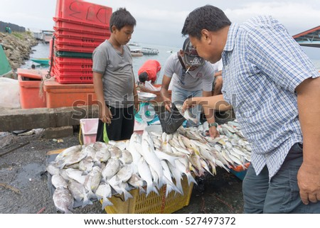 SEMPORNA,SABAH,MALAYSIA-November 30,2016: The sellers of seafood products such as fish,snails,squid and crab. They openly sale with low price and still fresh