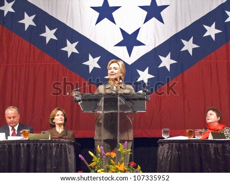 Sen. Hillary Clinton, speaks at a Little Rock, AK luncheon honoring the First Ladies of the state in front of the state flag November 17, 2004 in Little Rock, AK