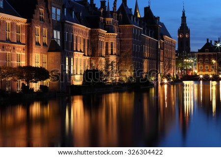 Senate building of the Dutch parliament complex illuminated at dusk in The Hague, The Netherlands. In the back, Grote Kerk tower clock indicates 9:35pm - stock photo