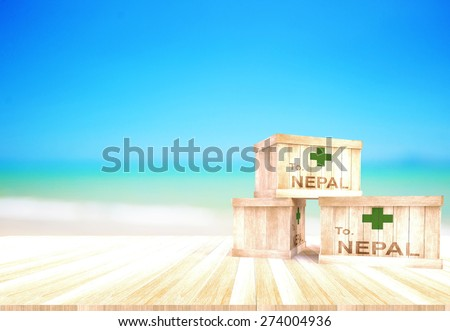 Send emergency aid to Nepal.Nepal earthquake.Wooden crate on wood floor and have a background of the sea.Pray for Nepal.Help Nepal - stock photo
