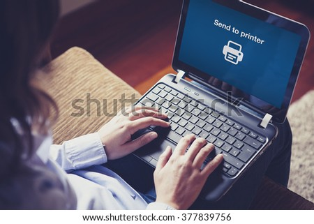 Send to printer message on a laptop computer. Woman working at home. - stock photo