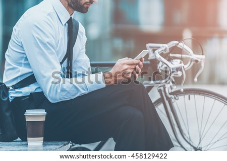 Sending business message. Cropped image of young businessman holding mobile phone while sitting near his bicycle outdoors - stock photo