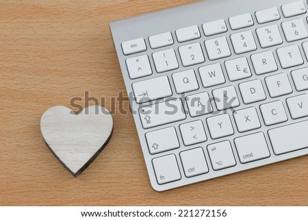 Sending love mails, wooden heart next to keyboard