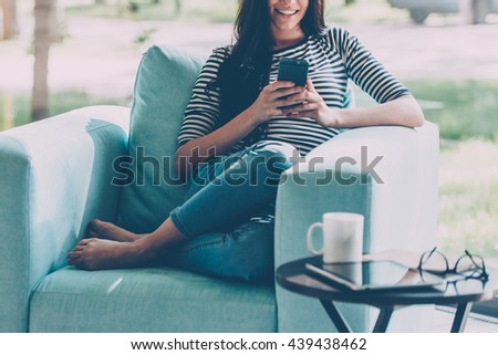 Sending lovely message. Beautiful young smiling woman looking at her smart phone while sitting in a big comfortable chair at home  - stock photo