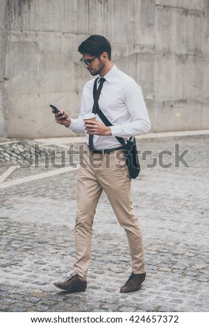 Sending quick business message. Full length of confident young man in glasses holding coffee cup and using his smart phone while walking outdoors - stock photo