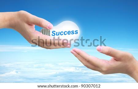sending success light bulb on women hand - stock photo