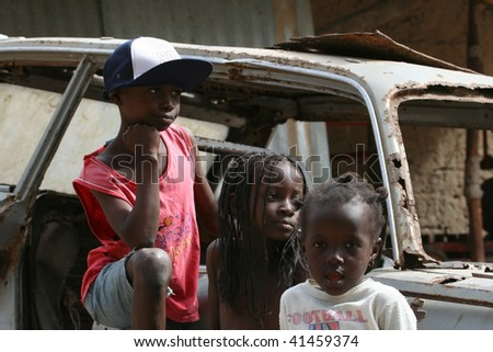 SENEGAL - FEBRUARY 18: Children of the Diola ethnic group pose with an abandoned car, February 18, 2007 in Casamance, Senegal - stock photo