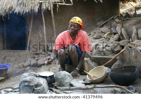 SENEGAL-FEBRUARY 15: Women Bedic ethnic cooking, the ethnic Bedic are less contact with the tourism in country Bassari, February 15, 2007 in Kedougou, Country Bassari, Senegal - stock photo
