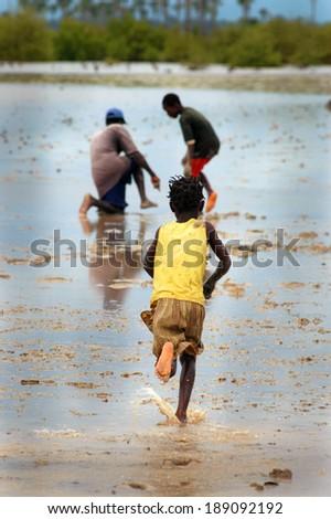 SENEGAL - SEPTEMBER 17: Little girl from the island of Carabane running away, on September 17, 2007 in Carabane, Casamance, Senegal - stock photo