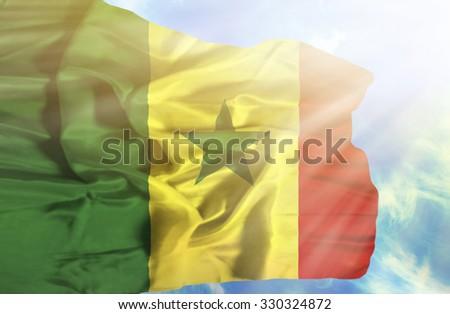 Senegal waving flag against blue sky with sunrays - stock photo