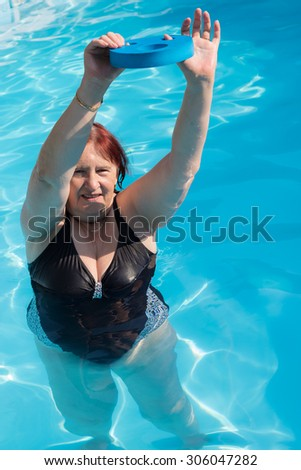 Senior active stretching out and exercising in an outdoor swimming pool on a sunny day - stock photo