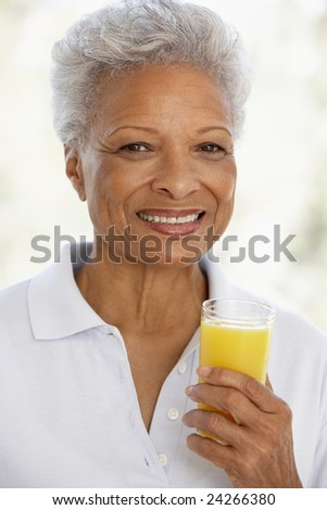 Senior Adult Holding A Glass Of Fresh Orange Juice, Smiling At The Camera - stock photo