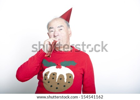 Senior adult man wearing Christmas jumper blowing party blower - stock photo