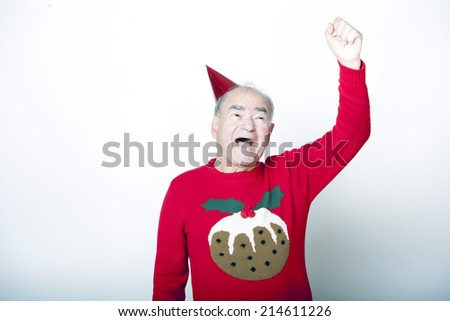 Senior adult man wearing Christmas jumper raising his arm in the air - stock photo