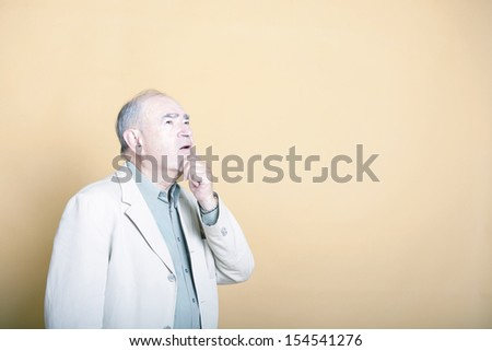 Senior adult man with his hand on his chin looking up inquisitively  - stock photo