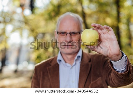 senior adult with gray hair and eyeglasses, elegant dressed, showing an green apple standing outside - stock photo