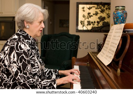 Senior adult woman in active retirement living plays the piano in her home. - stock photo
