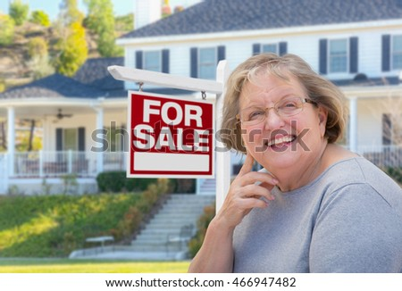 Senior Adult Woman in Front of Home For Sale Real Estate Sign and Beautiful House.