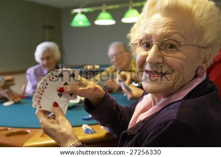 Senior adults playing bridge - stock photo