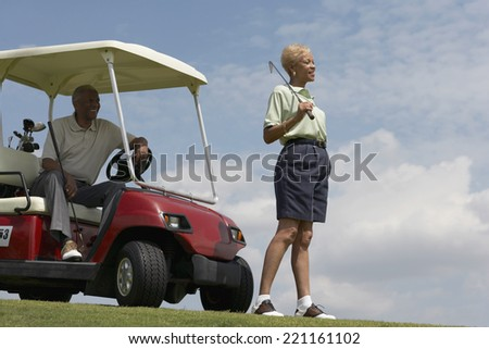 Senior African American couple with golf cart - stock photo